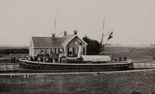 """Omstreeks 1900. Stoomschip, de """"Sofia"""" wordt geschut in de Wetsingersluis; op de achtergrond de sluismeesterswoning."""